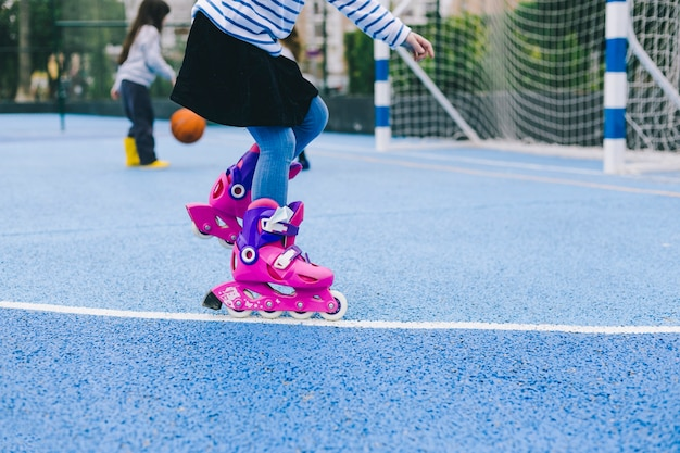 Crop girl riding roller skates on sports ground