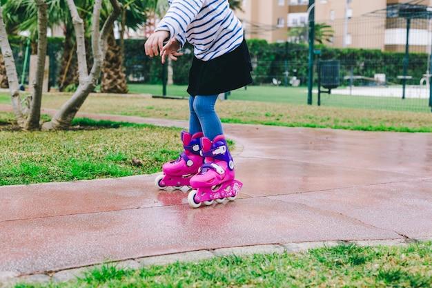 Crop girl riding roller skates