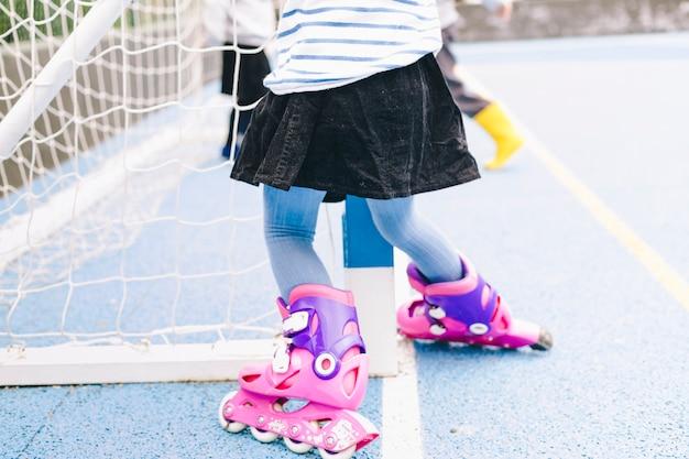 Crop girl on roller skates near net