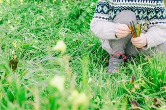 Crop girl sitting on garden grass