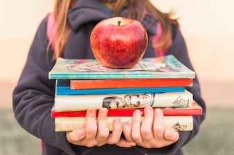 Crop girl with books and apple