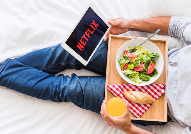 Crop guy eating and watching series on bed
