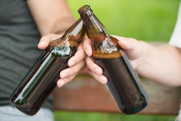 Crop guys clinking bottles on bench in park
