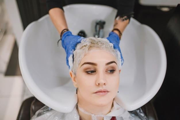 Hairstylist del raccolto che lava capelli con lo sciampo
