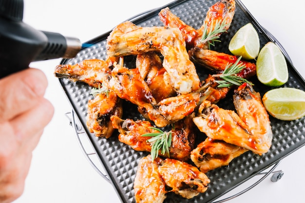 Crop hand blowtorching chicken wings
