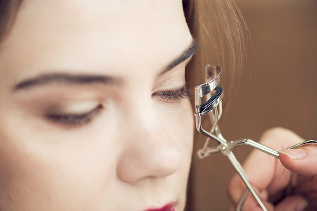 Crop hand curling eyelashes of model