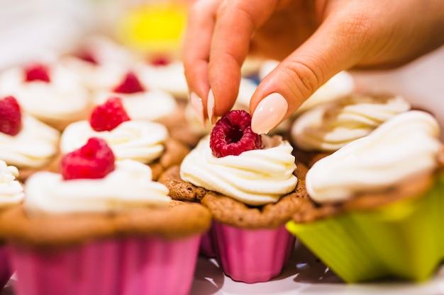 Crop mano decorando muffin con lamponi