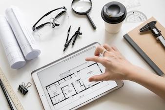 Crop hand enlarging plan on tablet