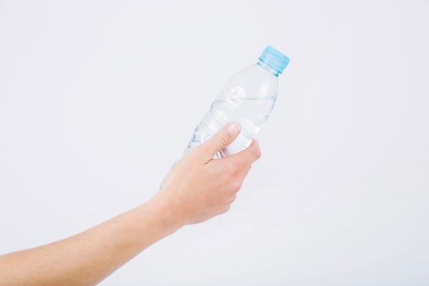 Кастрюля, держащая бутылку с водой