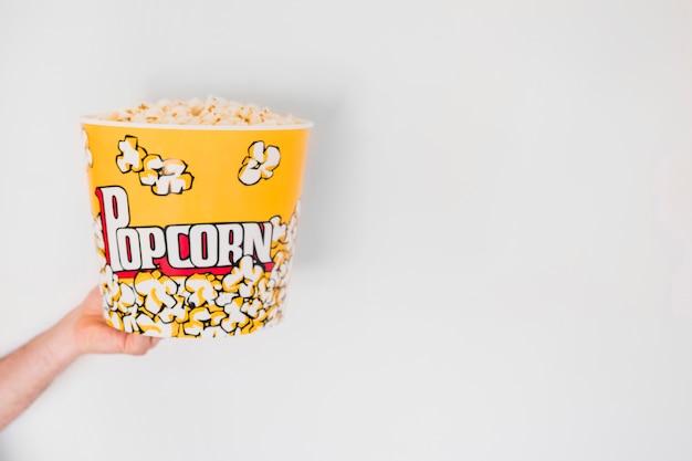Crop hand holding bucket of popcorn