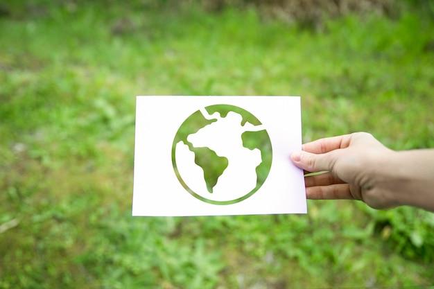 Crop hand holding earth symbol