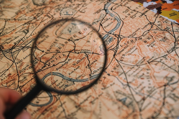 Crop hand holding magnifying glass over map