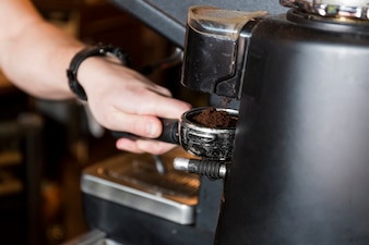 Crop hand holding portafilter with coffee