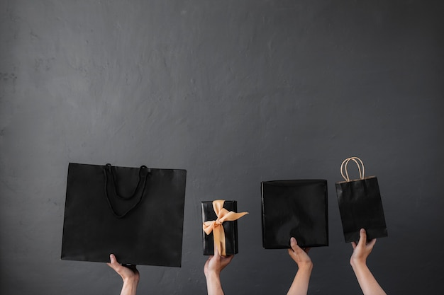Crop of hand holding shopping bag or goodie bag for shopaholic online shopping background concept