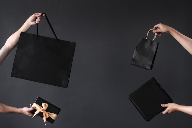 Crop of hand holding shopping bag or goodie bag for shopaholic or online shopping background