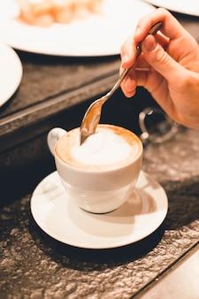Crop hand mixing coffee