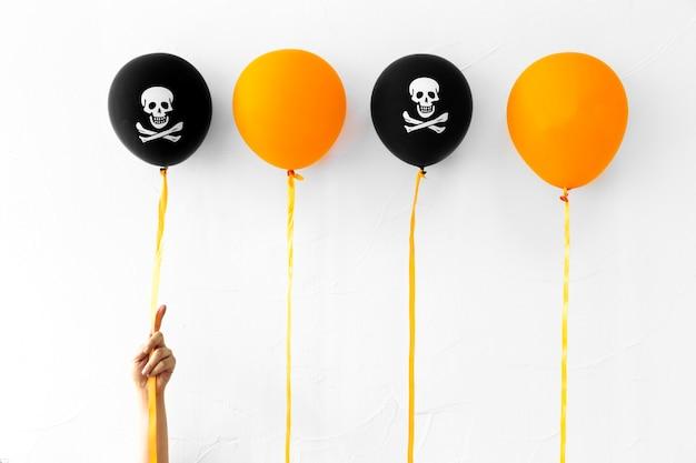 Crop hand near halloween balloons