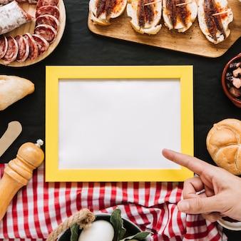 食べ物の中の空のフレームを指す作物の手
