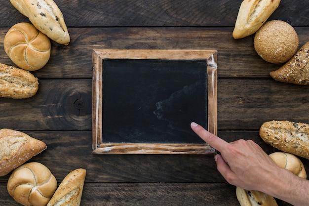 La mano del raccolto che indica alla lavagna vicino al pane