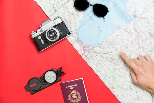 Ritaglia la mano che punta alla mappa vicino a forniture turistiche