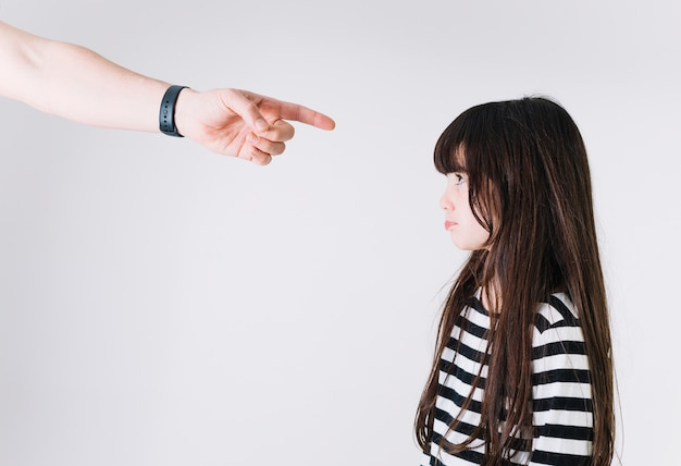 Crop hand pointing at upset girl