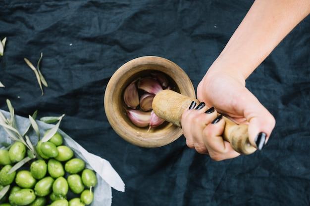 Crop hand pressing garlic
