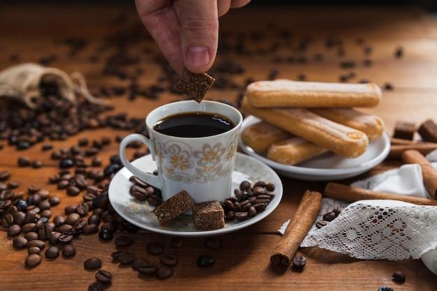 Crop hand putting sugar into coffee