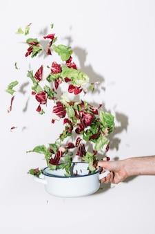 Crop hand shaking saucepan with salad
