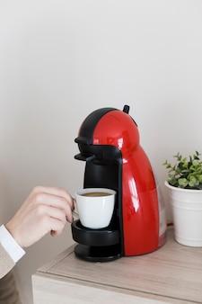 Crop hand taking drink from coffee machine