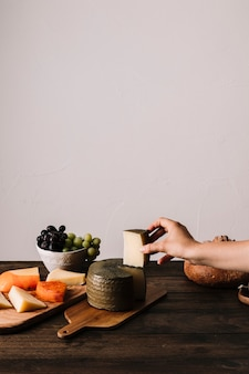 Crop hand taking piece of cheese from table