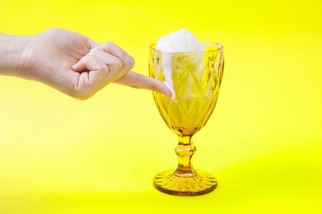 Crop hand touching melting ice-cream on cup