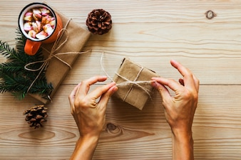 Crop hand tying rope on gift box