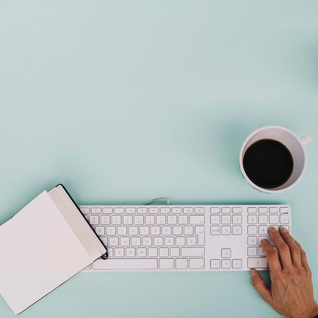 Crop hand using keyboard near notebook and coffee