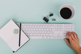 Crop hand using keyboard near stationery and coffee