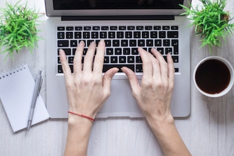 Crop hand using laptop near coffee and notebook