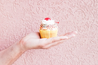 Crop hand with cupcake
