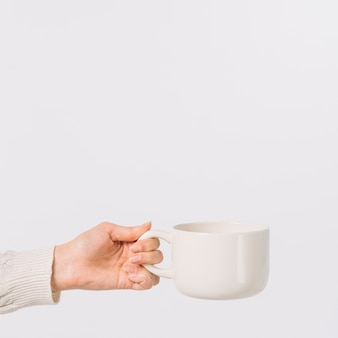 Crop hand with hot drink