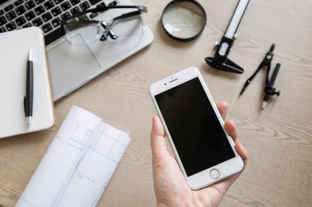 Ritaglia la mano con lo smartphone vicino alla stesura di forniture e laptop