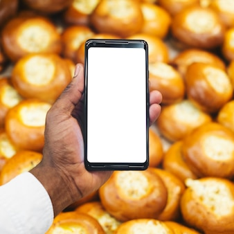 Crop hand with smartphone on pastry background