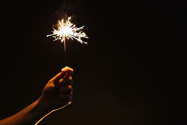 Crop hand with sparkler