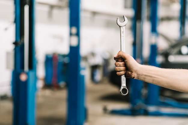 Crop hand with wrench in workshop