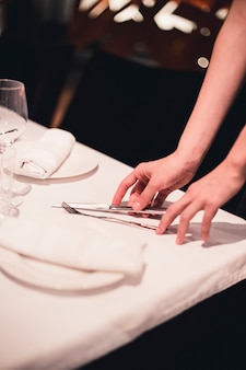 Crop hands arranging cutlery on table