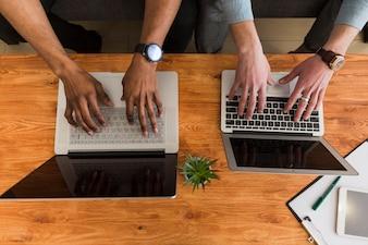 Crop hands browsing laptops