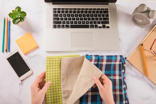 Crop hands choosing cloth near laptop