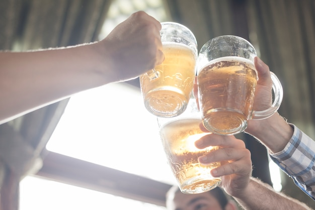 Crop hands clinking mugs of booze in bar