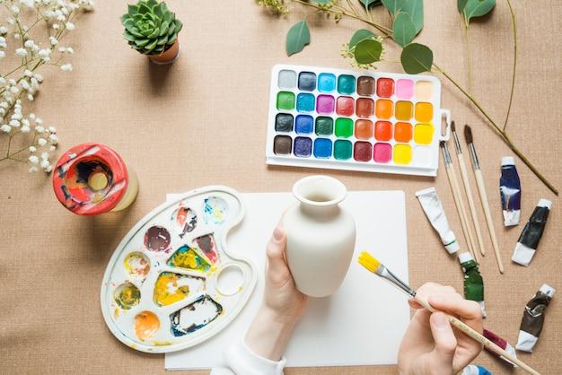 Crop hands coloring vase
