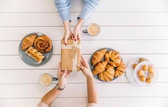 Crop hands giving present during breakfast