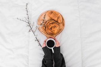Crop hands holding coffee near buns