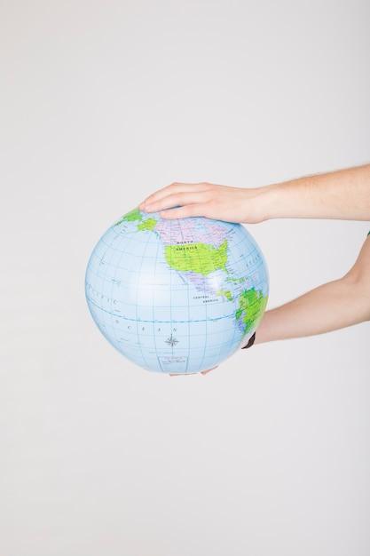 不規則な形の地球儀を保持する作物の手