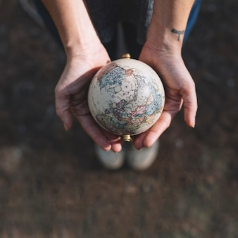 Crop hands holding globe